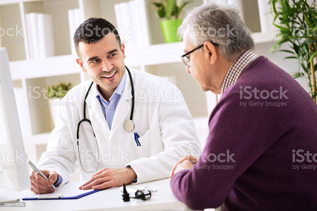 Doctor explaining prescription to senior patient stock photo
