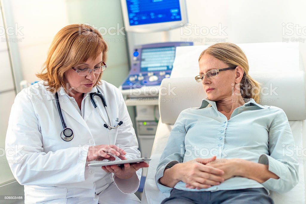 Doctor explaining test results to her patient using digital tablet stock photo