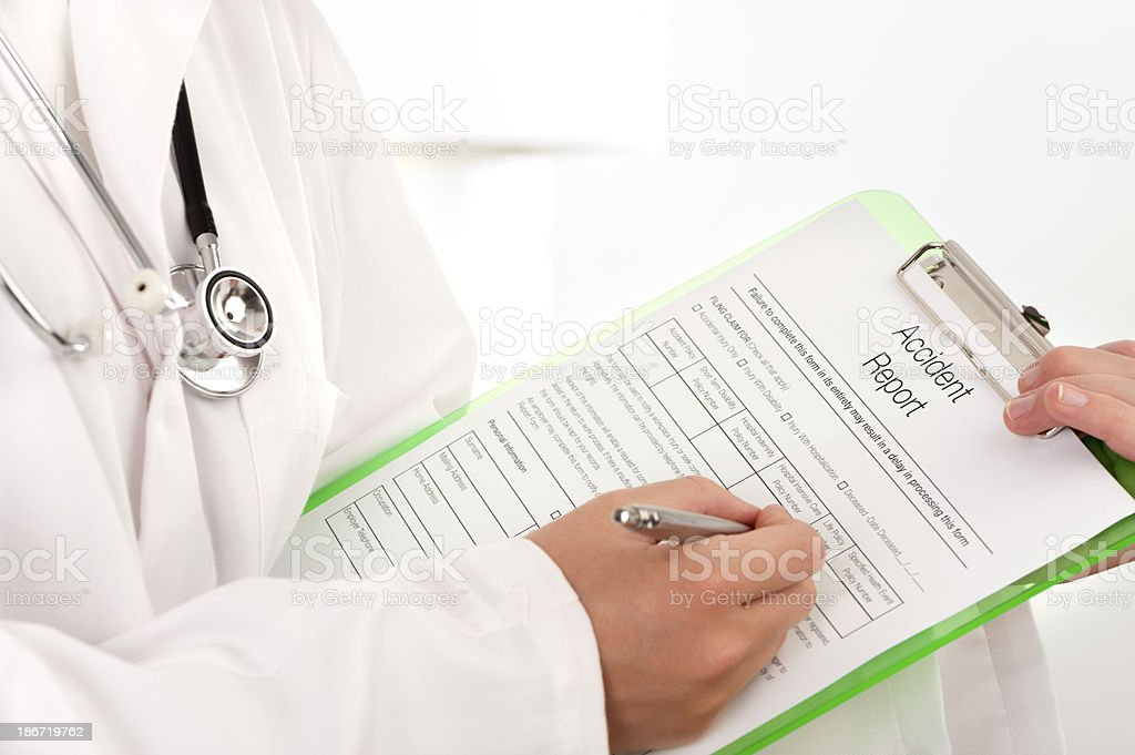Doctor filling out an accident report royalty-free stock photo