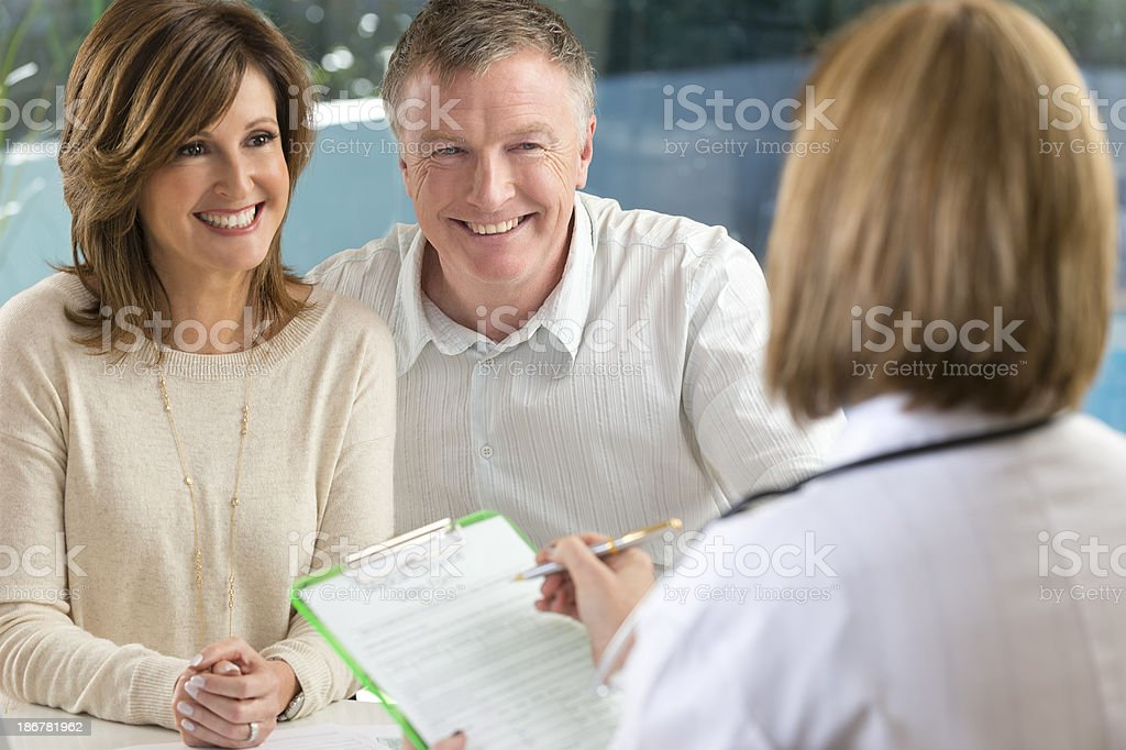 Doctor filling out insurance form with mature couple stock photo