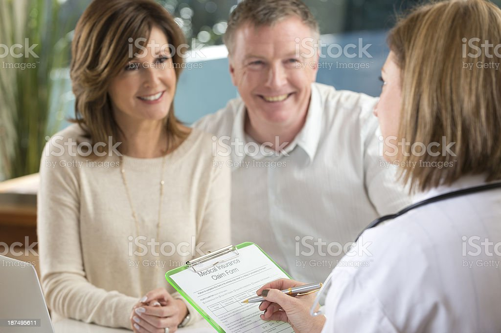 Doctor filling out insurance form with mature couple royalty-free stock photo