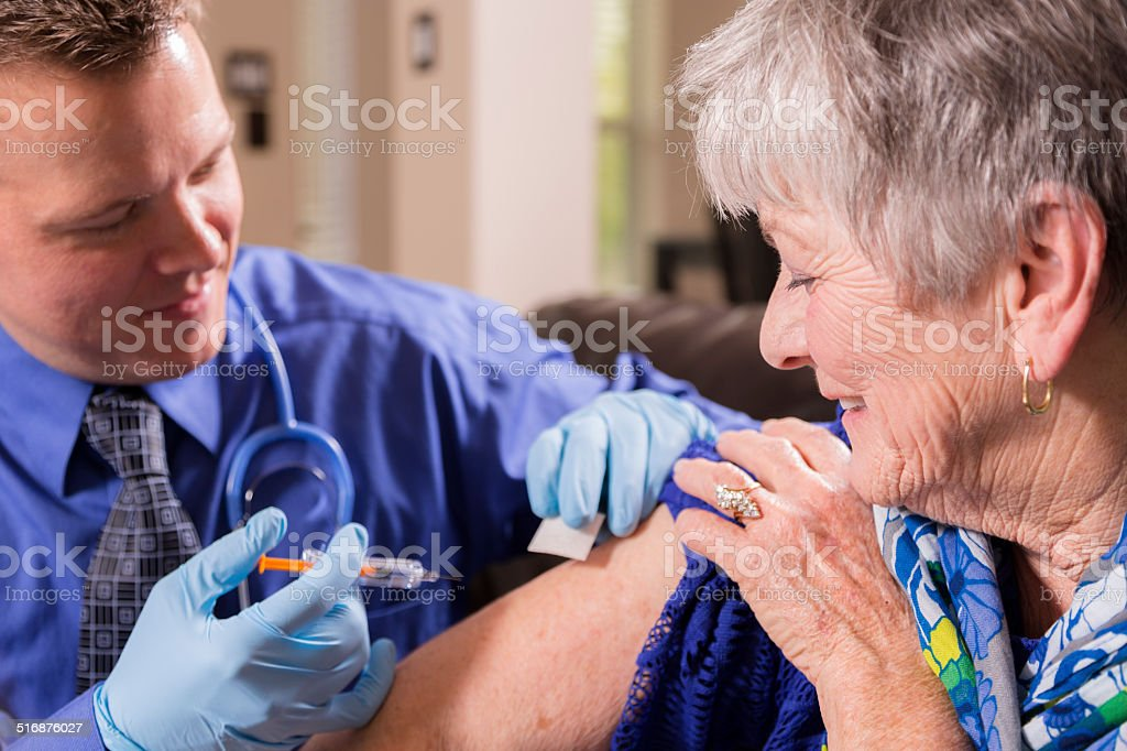 Doctor gives senior woman patient a vaccine.  Nursing home. stock photo