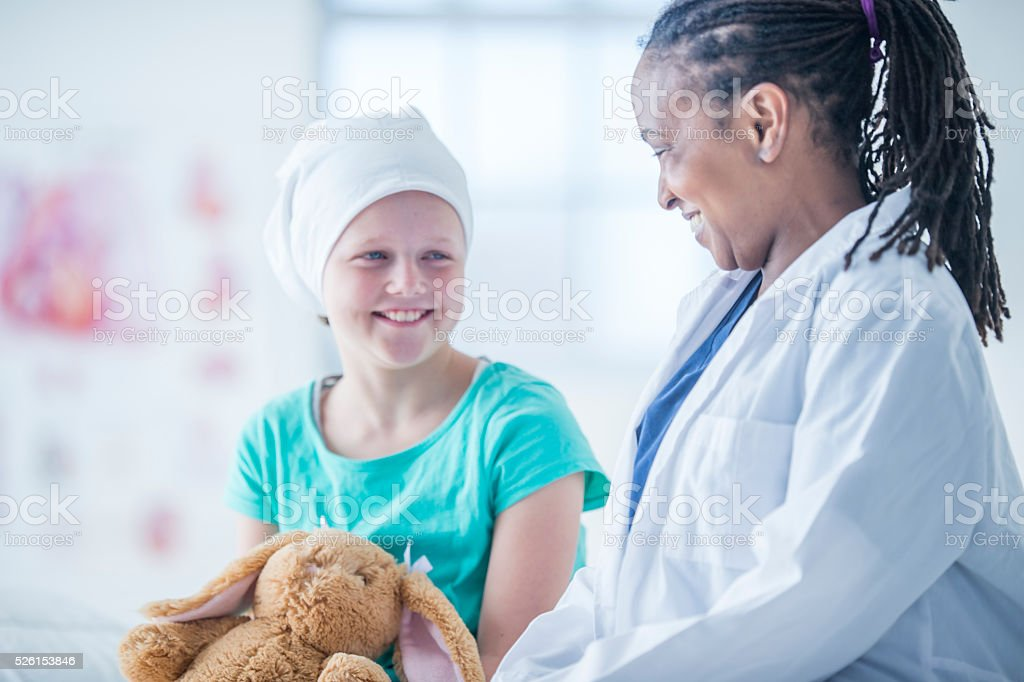 Doctor Giving a Little Girl a Stuffed Animal stock photo