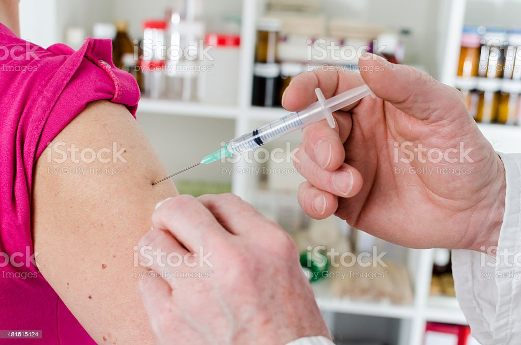 Doctor giving an injection to his patient stock photo
