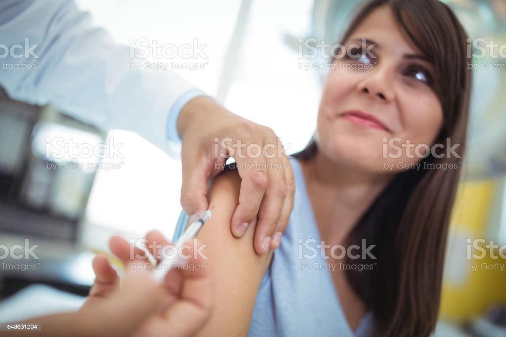 Doctor giving an injection to the patient stock photo