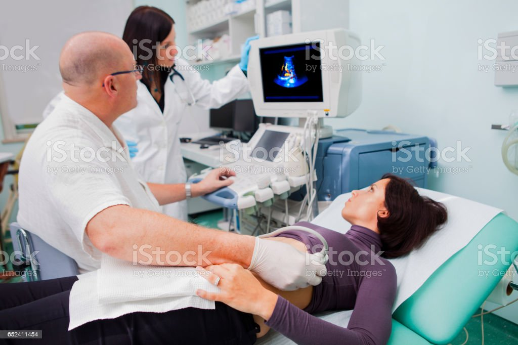 Doctor giving beautiful young patient an ultra sound stock photo