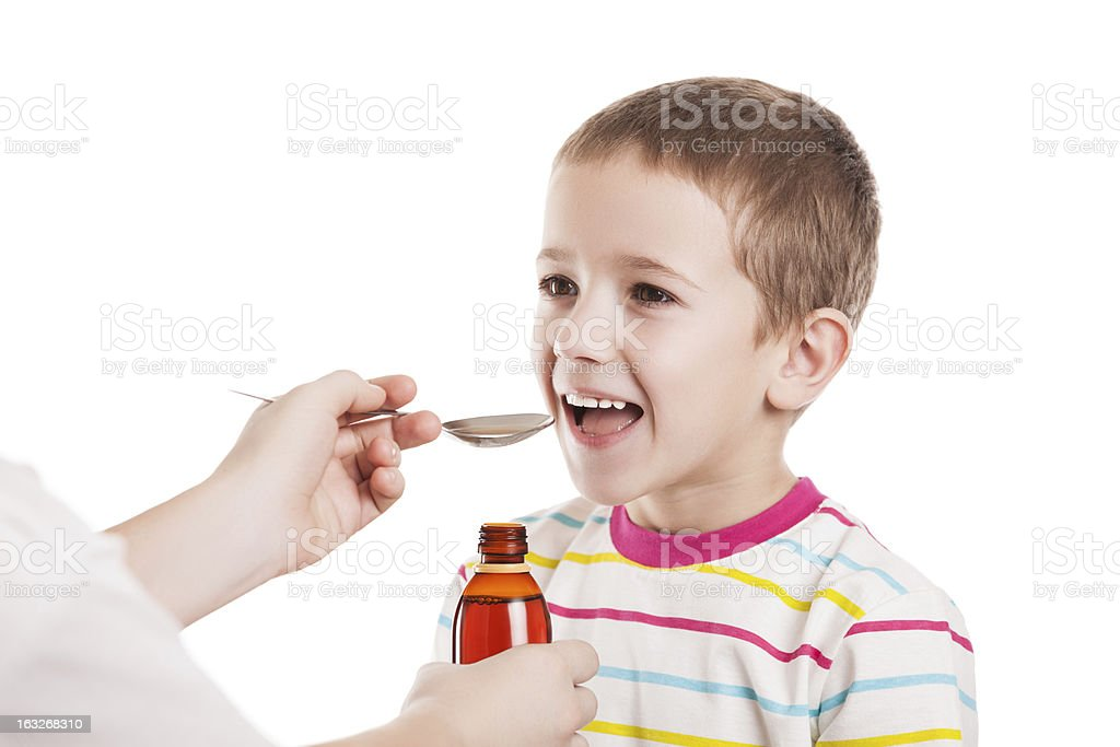 Doctor giving spoon of syrup to child boy royalty-free stock photo