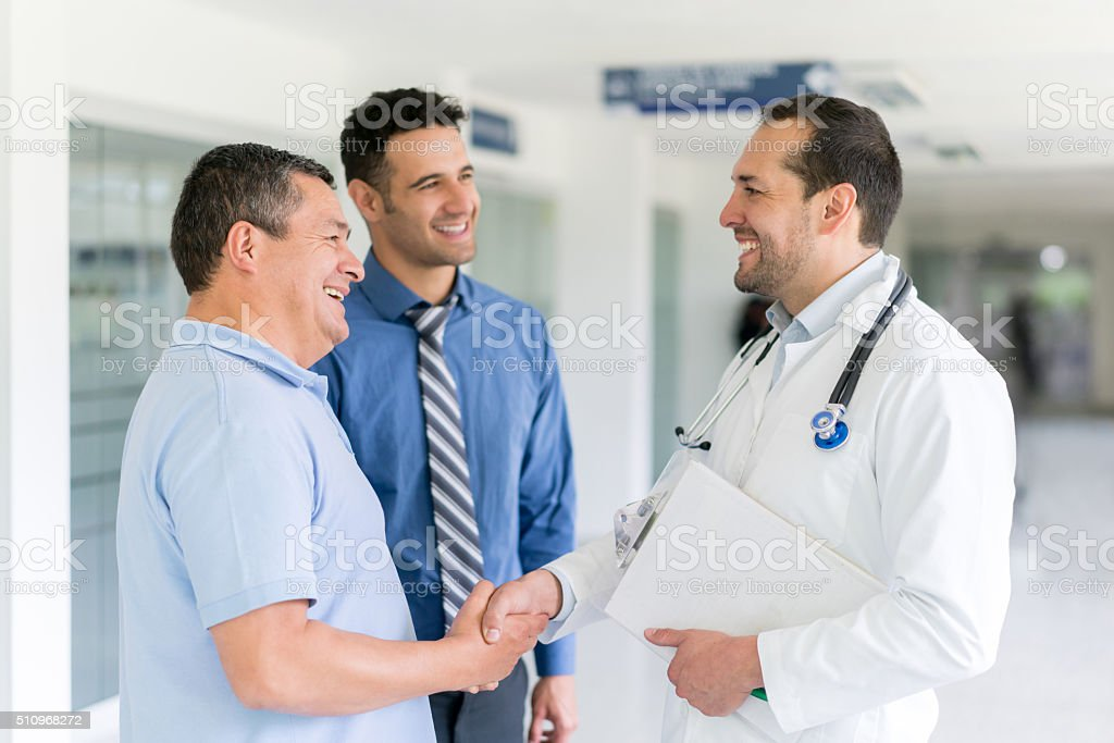 Doctor greeting patient with a handshake stock photo