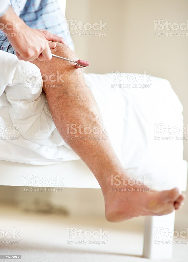 Doctor hand checking old man knee using a reflex hammer stock photo