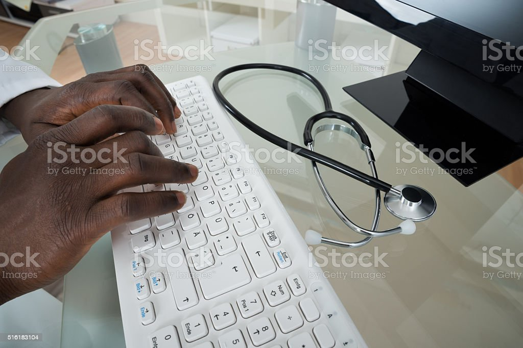 Doctor Hands Typing On Computer Keyboard stock photo