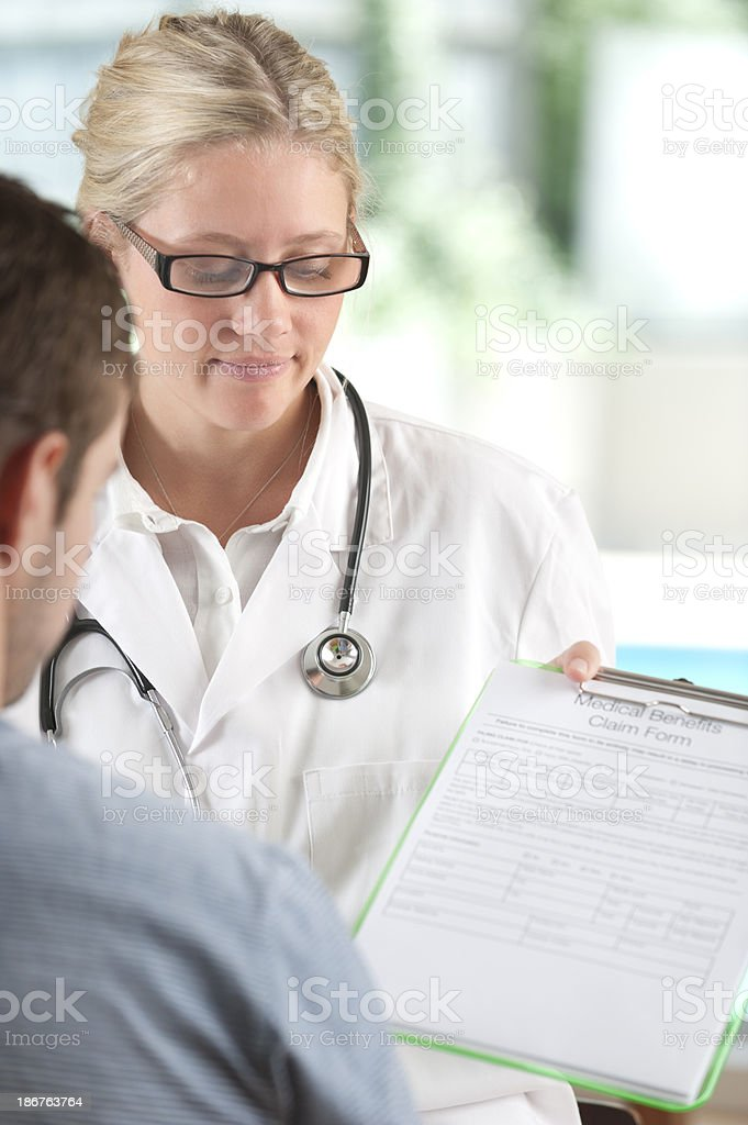 Doctor helping patient fill out form stock photo