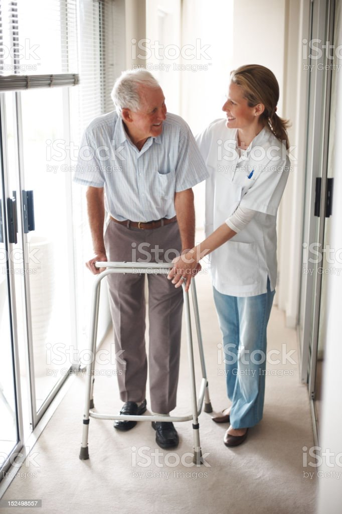 Doctor helping senior man on a walker royalty-free stock photo
