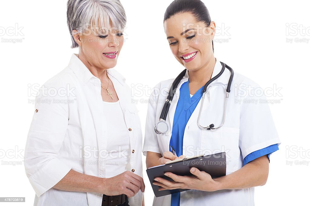 doctor helping senior woman with medical form stock photo