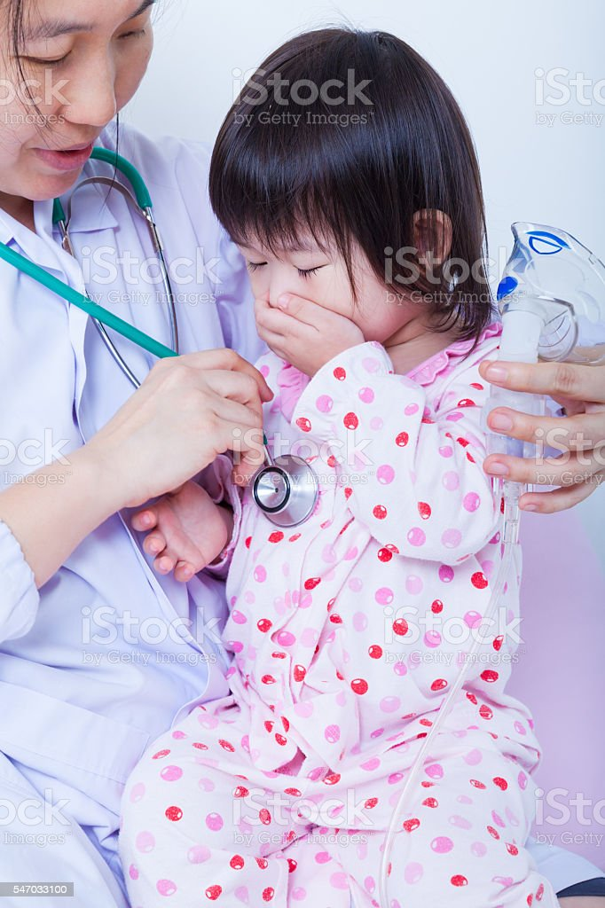Doctor helps little asian girl taking respiratory, inhalation th stock photo