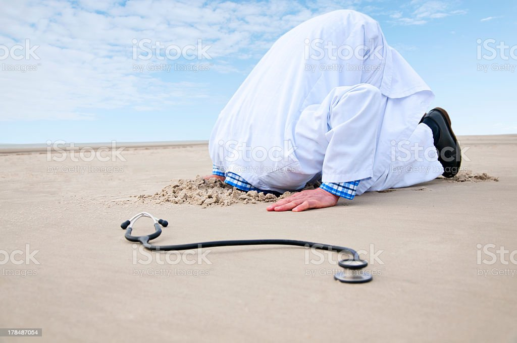 Doctor Hiding Head In Sand stock photo