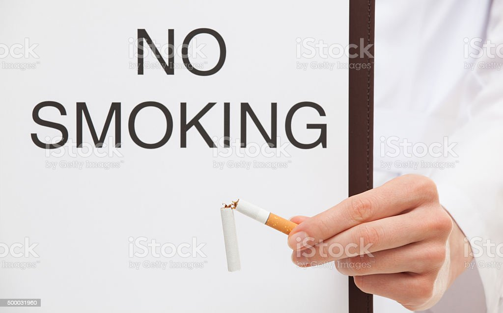 Doctor holding a clipboard with text 'No smoking' stock photo