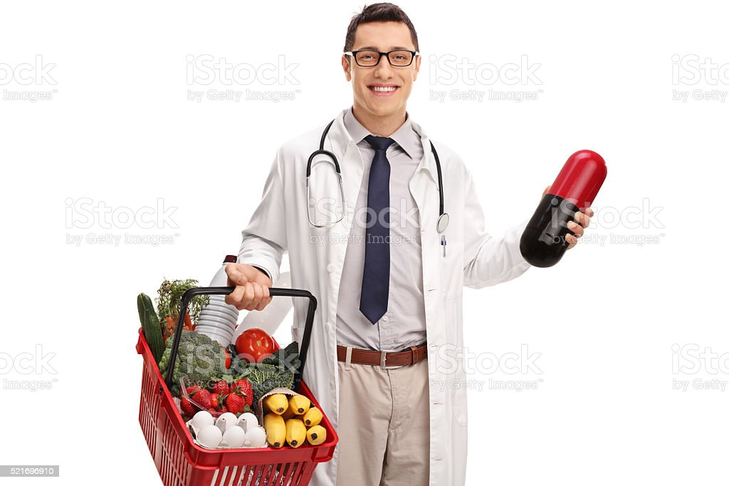 Doctor holding a huge pill and groceries stock photo