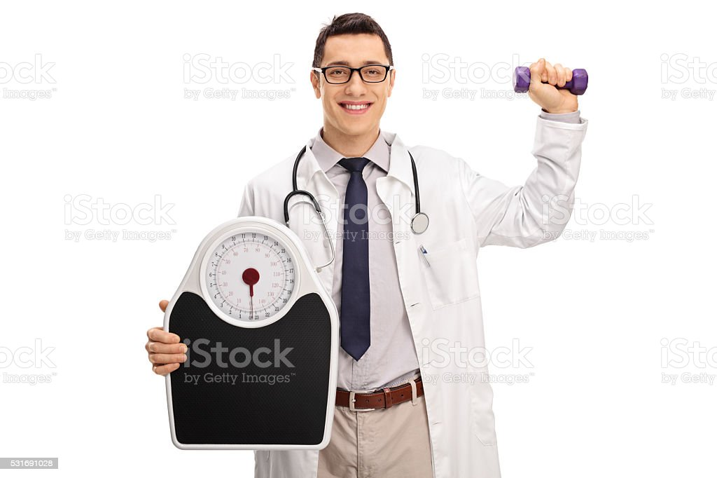 Doctor holding a weight scale and a dumbbell stock photo