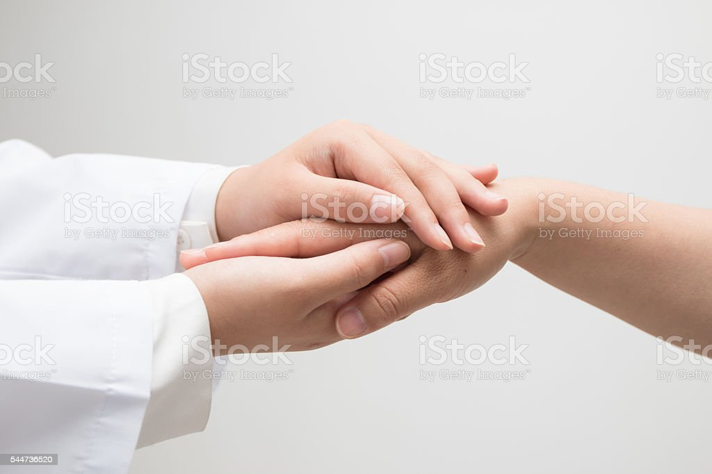 Doctor holding a woman hand stock photo
