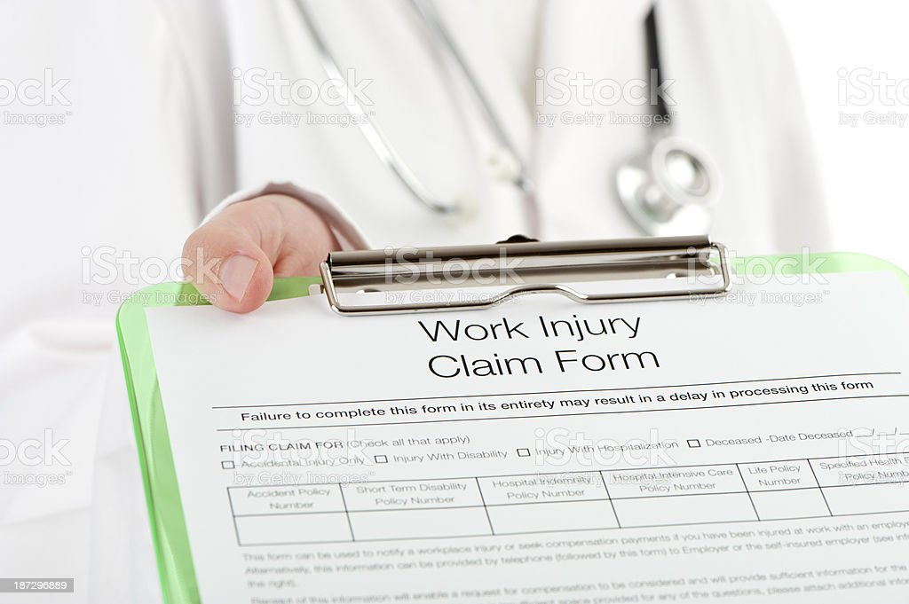 Doctor holding a work injury claim form royalty-free stock photo