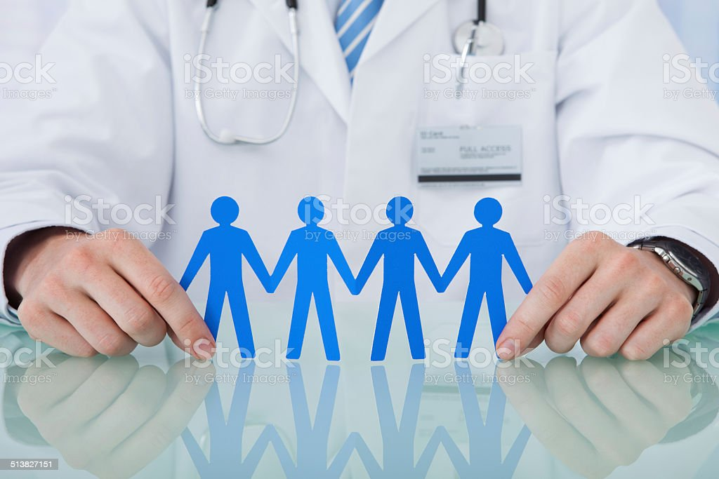 Doctor Holding Blue Paper People Chain At Desk stock photo