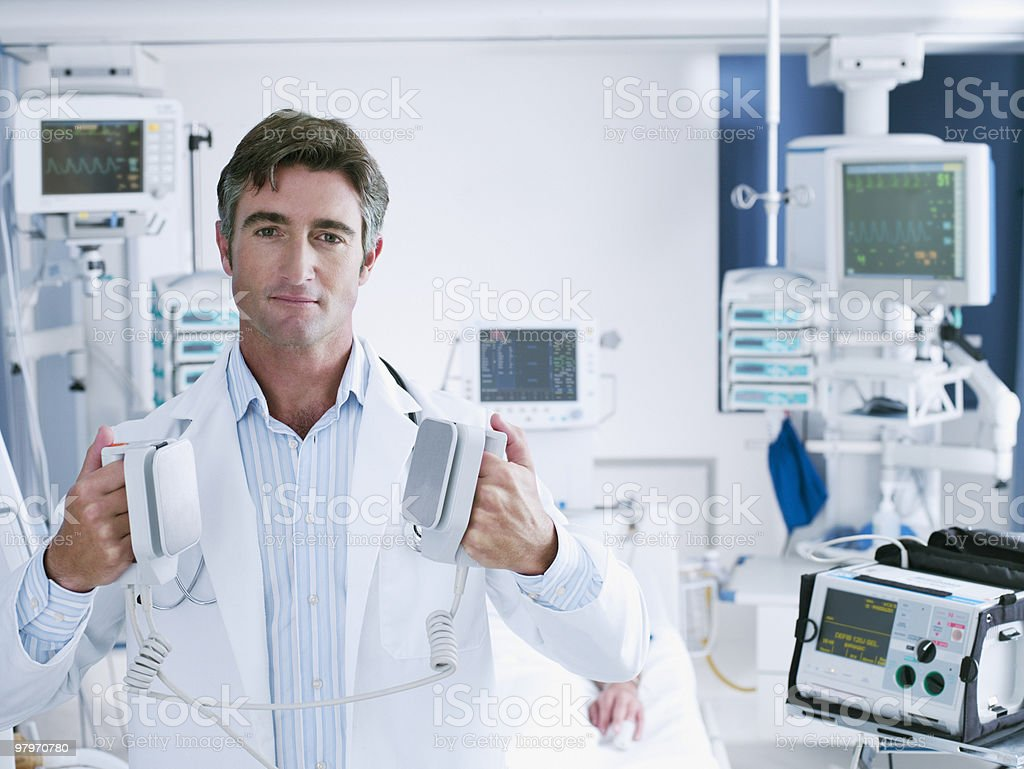 Doctor holding defibrillator paddles in hospital room stock photo