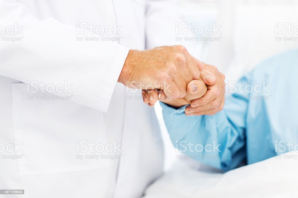 Doctor Holding Female Patient's Hand stock photo