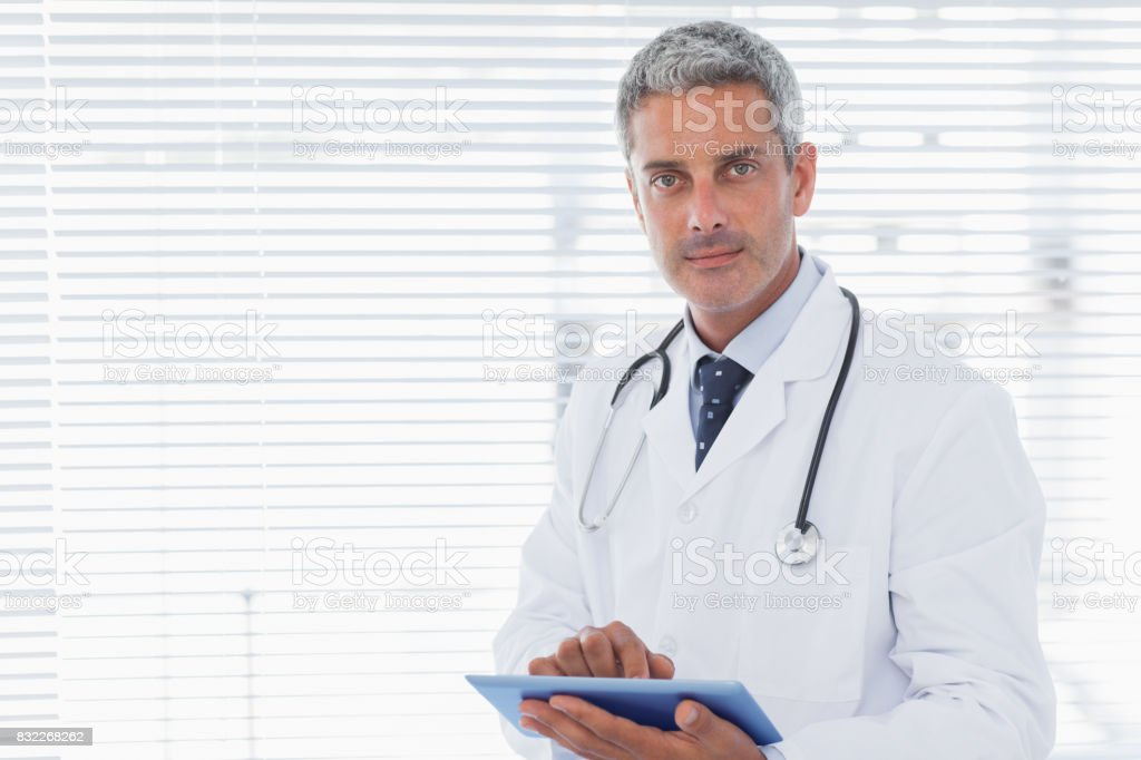 Doctor holding his tablet pc and looking at camera stock photo