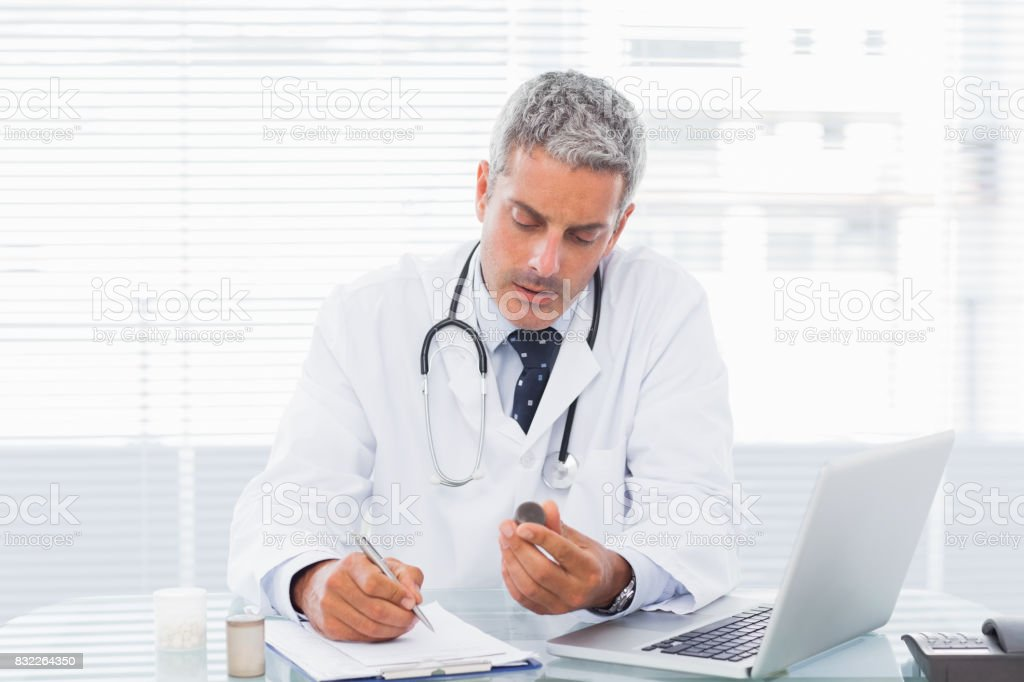 Doctor holding medication and writing a prescription stock photo