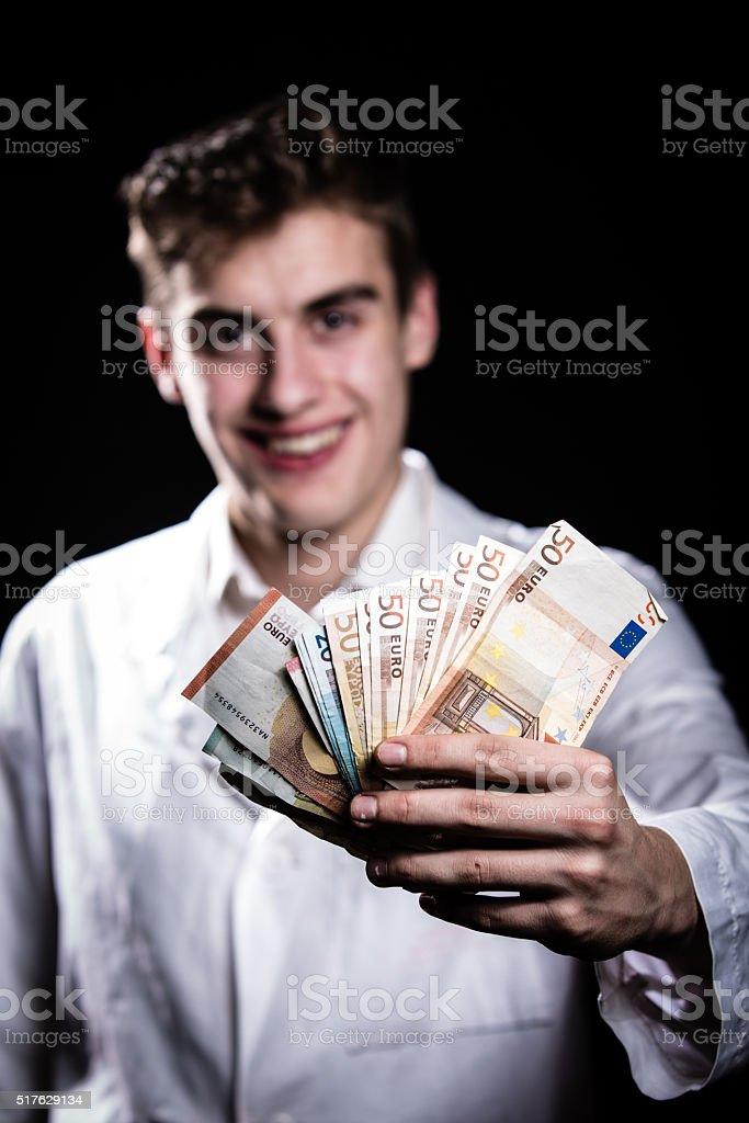Doctor holding money.Medic salary,high paid job,medical insurance stock photo