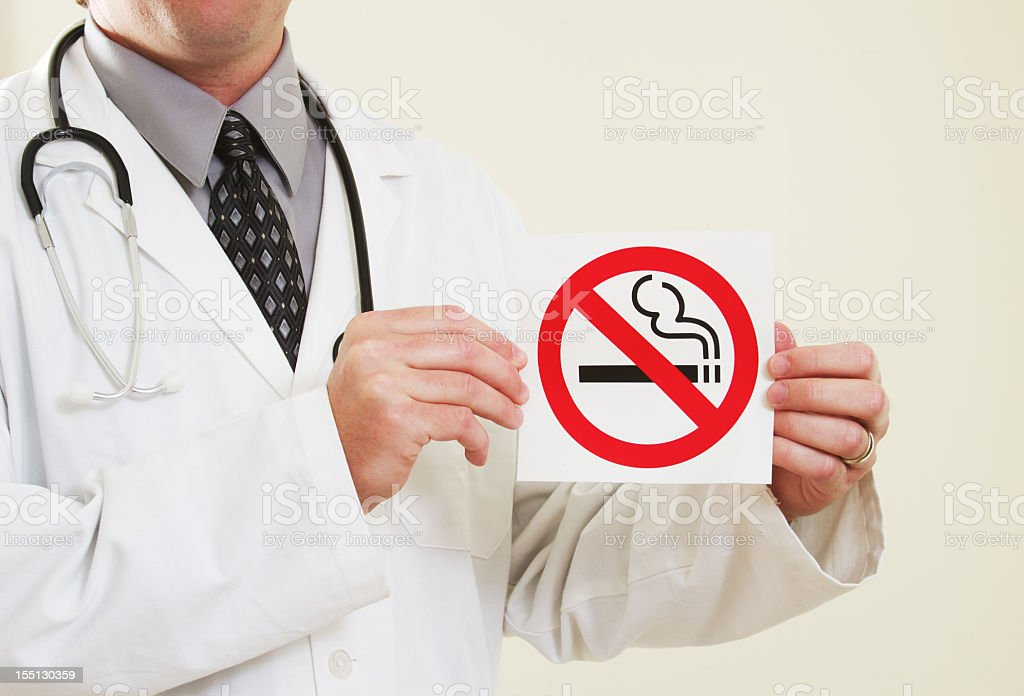 Doctor Holding No Smoking Sign stock photo