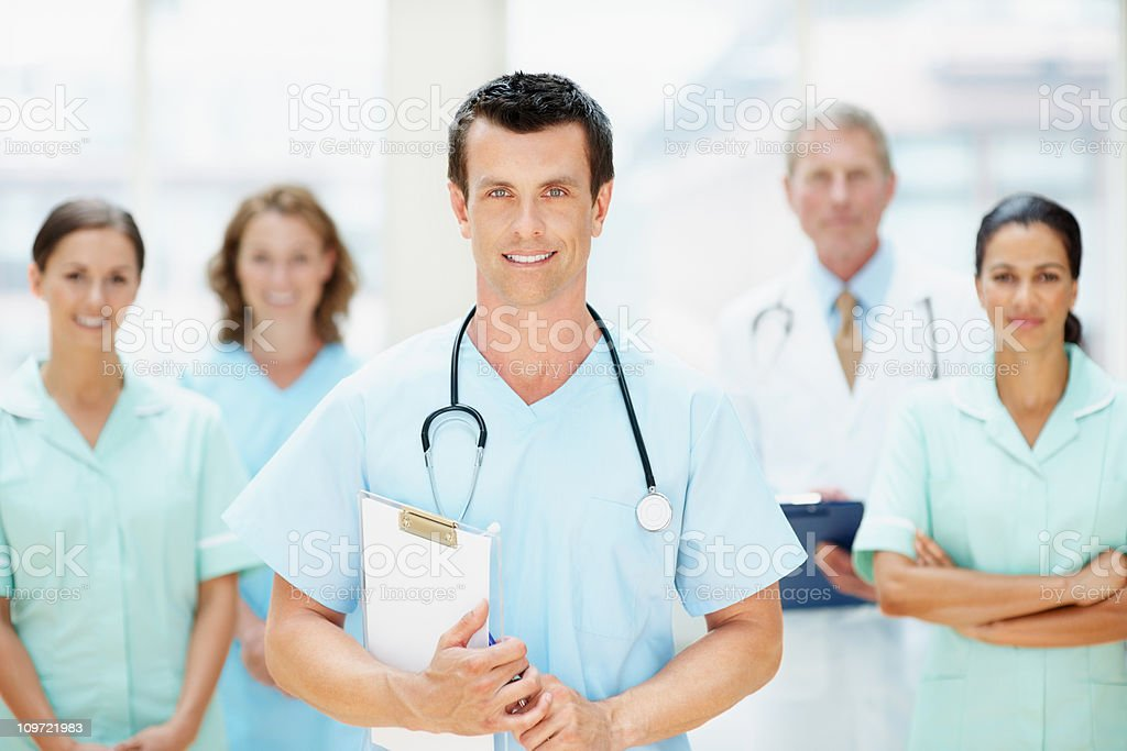 Doctor holding notepad with blurred team in background royalty-free stock photo