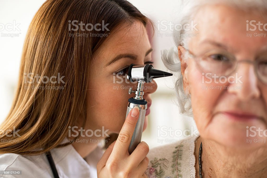 Doctor holding otoscope and examining ear of senior woman stock photo