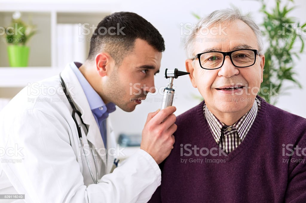 Doctor holding otoscope and examining patient ear stock photo