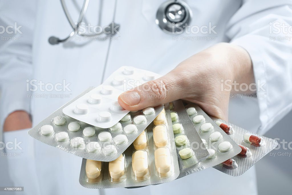 Doctor holding out several packs of medicine stock photo