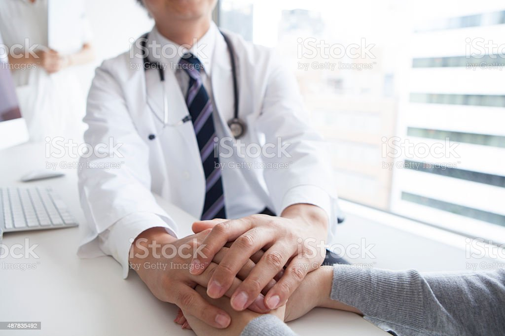 Doctor holding patient hand to give a support stock photo