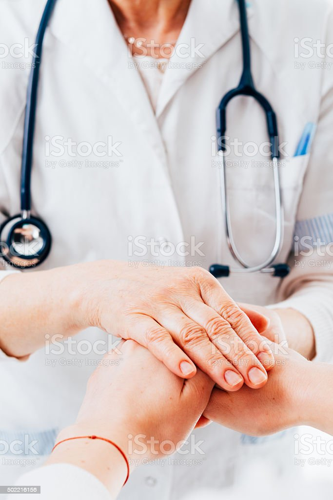 Doctor holding patient hands stock photo