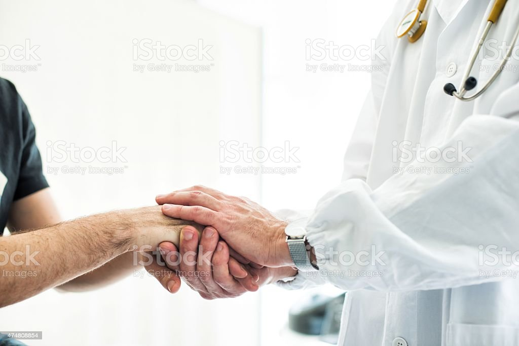 Doctor Holding Patient's Hands stock photo