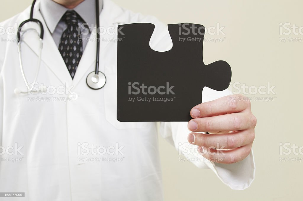 Doctor holding Puzzle Piece stock photo
