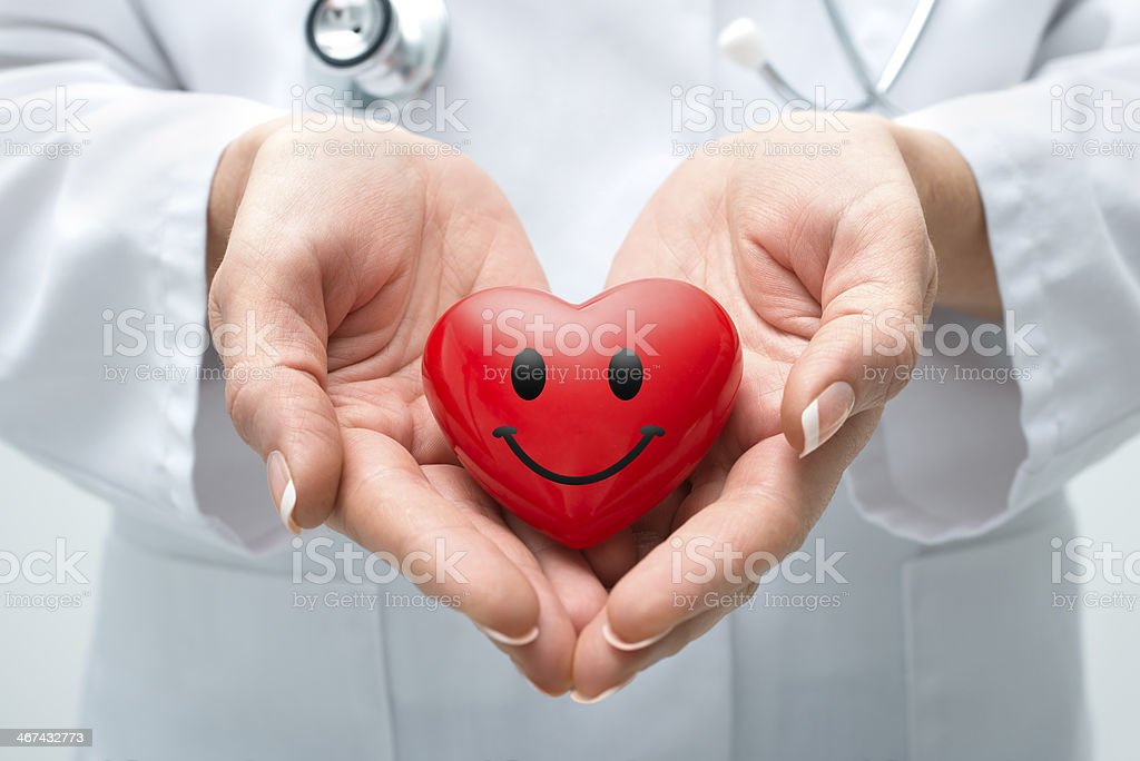 Doctor holding smiling heart stock photo