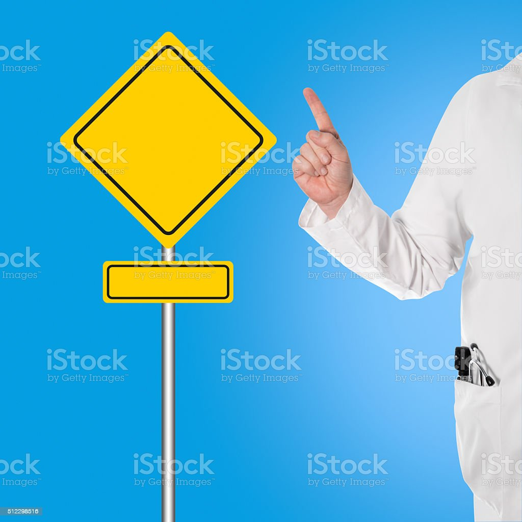 Doctor holding thumbs up, and pointing to a sign stock photo