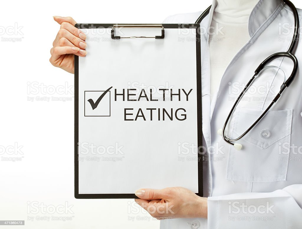Doctor holding up clipboard saying healthy eating royalty-free stock photo