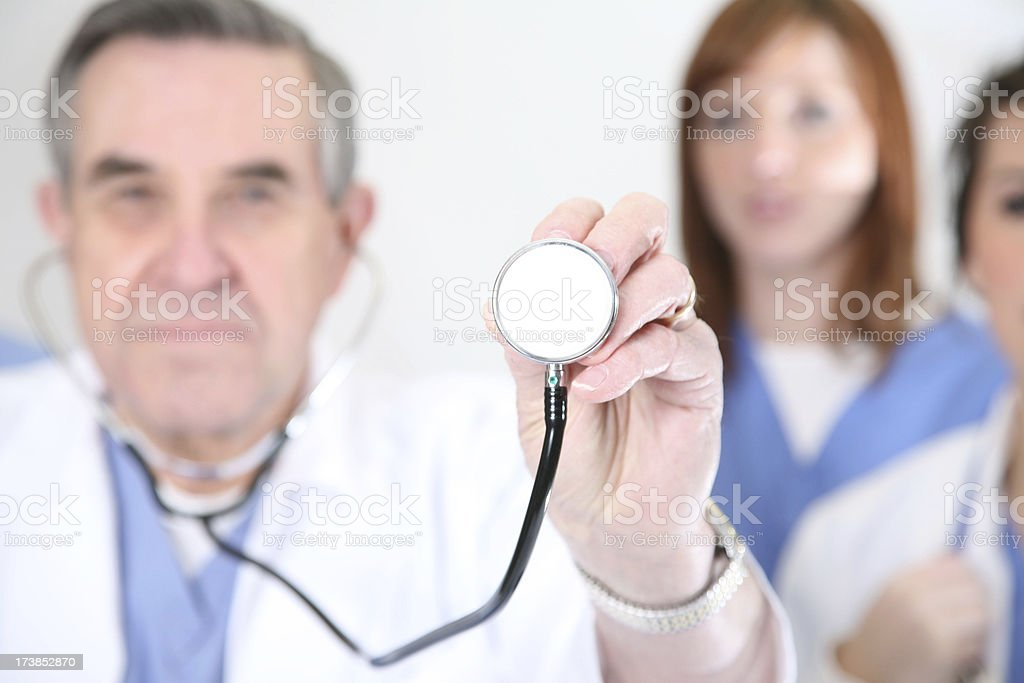 Doctor holding up stethoscope with peers behind him royalty-free stock photo