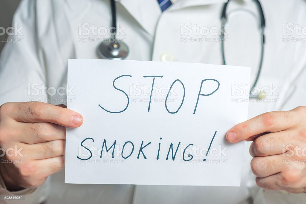 Doctor holds a clipboard with stop smoking label stock photo