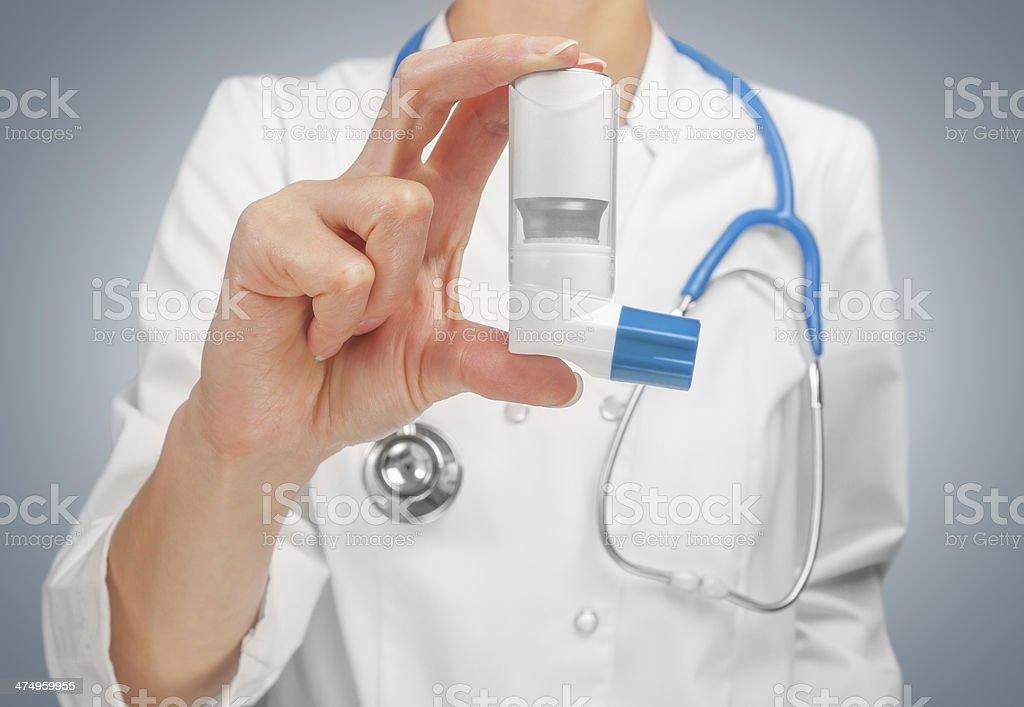 Doctor holds inhaler stock photo