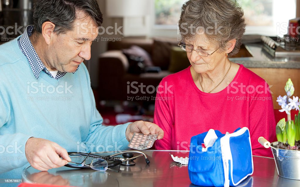 Doctor home visit with senior patient advising on tablets royalty-free stock photo