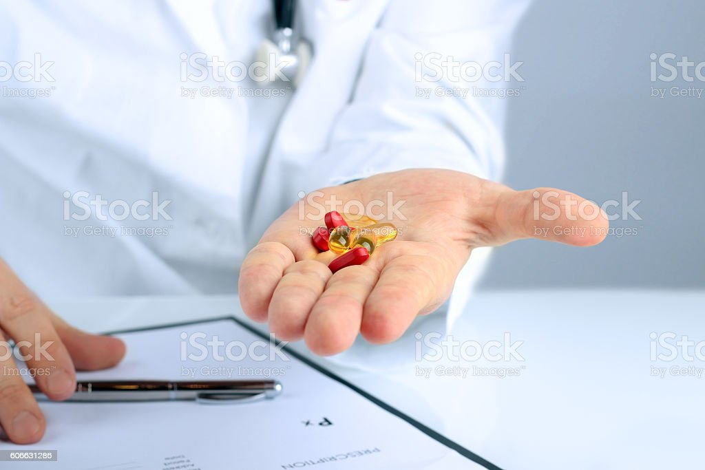 Doctor in a white  labcoat giving  pills stock photo