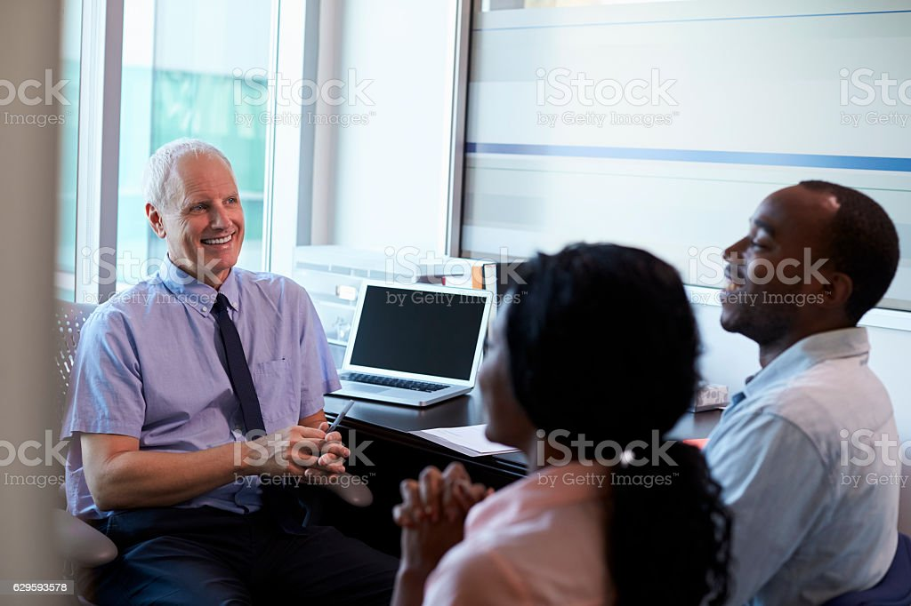 Doctor In Consultation With Couple In Office stock photo