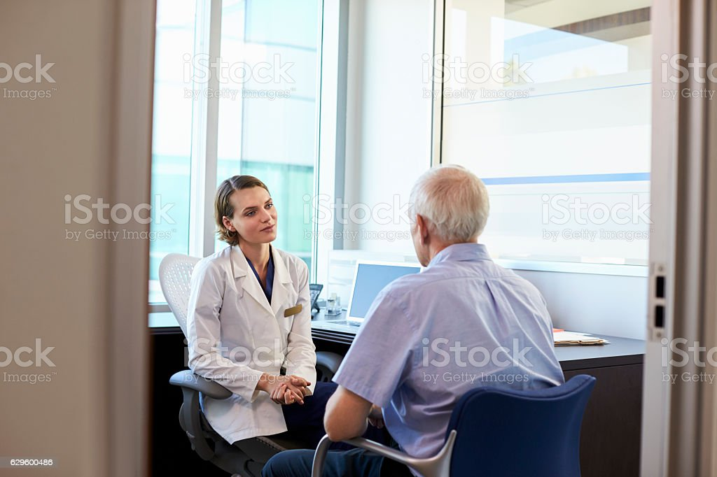 Doctor In Consultation With Male Patient In Office stock photo