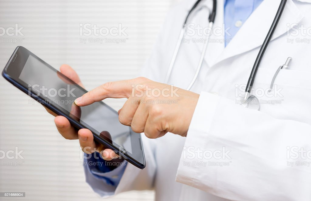 doctor in office working tablet computer stock photo